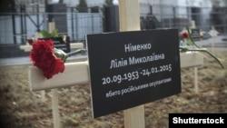 Памятный крест с именем одной из жертв обстрела в Мариуполе