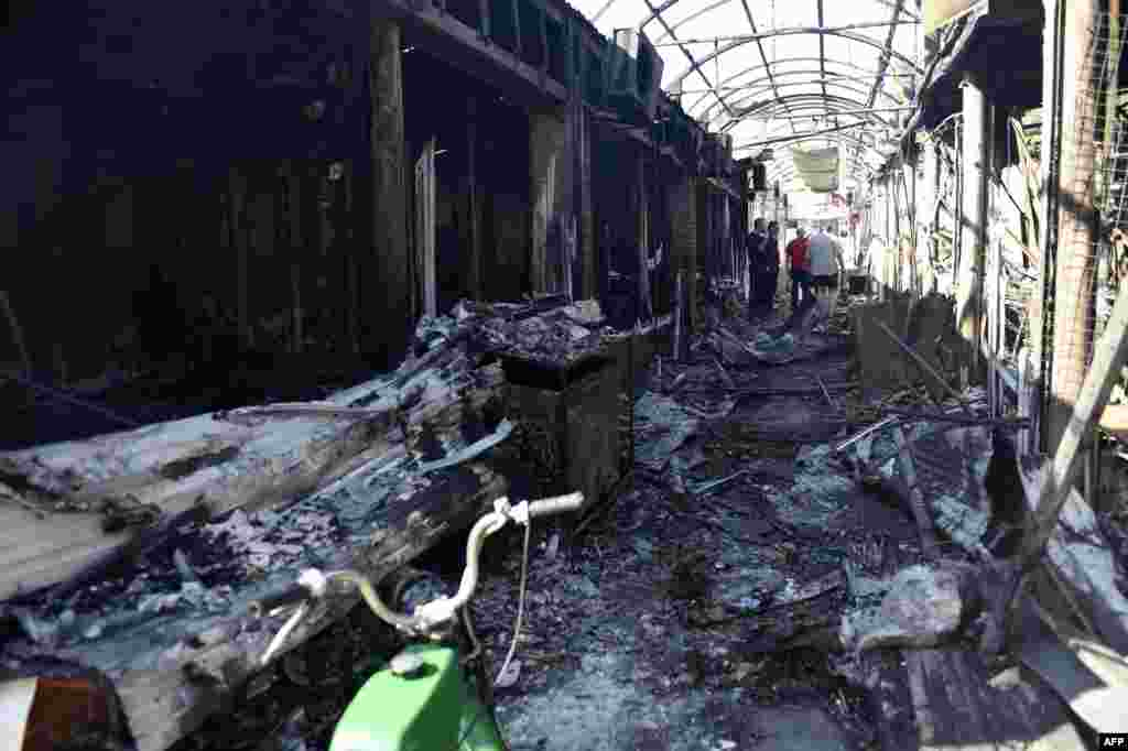 Ukraine -- People walk in a market gallery destroyed by shelling, in the Kievsky district in Donetsk, September 15, 2014