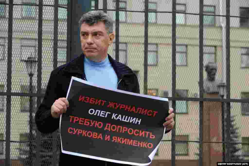 Борис Немцов держит плакат с требованием начать расследование по делу избиения оппозиционного журналиста Олега Кашина