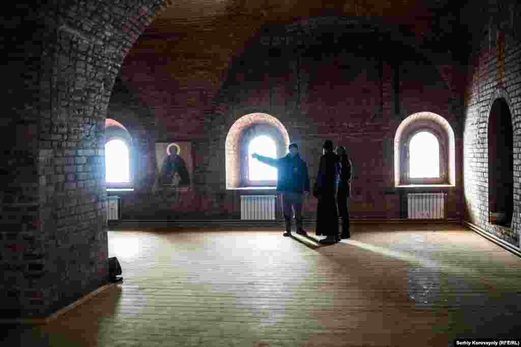 Настоятель Дионисий, староста монастыря Иван и Кирилл стоят в новом здании церкви. Постройку финансирует государство