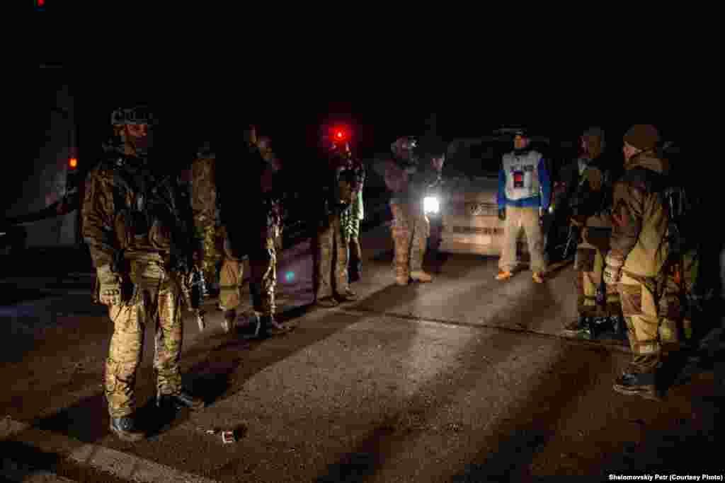 Наблюдатель ОБСЕ стоит между военнослужащими конфликтующих сторон