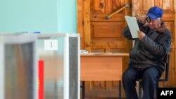 Мужчина читает бюллетень на выборах в Костроме