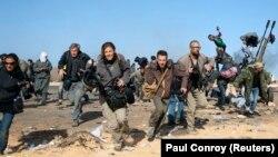 Репортеры New York Times, Getty Images и Reuters бегут в укрытие во время бомбардировки правительственных войск Ливии вблизи нефтяного завода Рас эль-Ануф в марте 2011 года