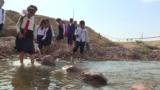 Дети из поселка в Таджикистане переходят реку вброд, чтобы добраться до школы
