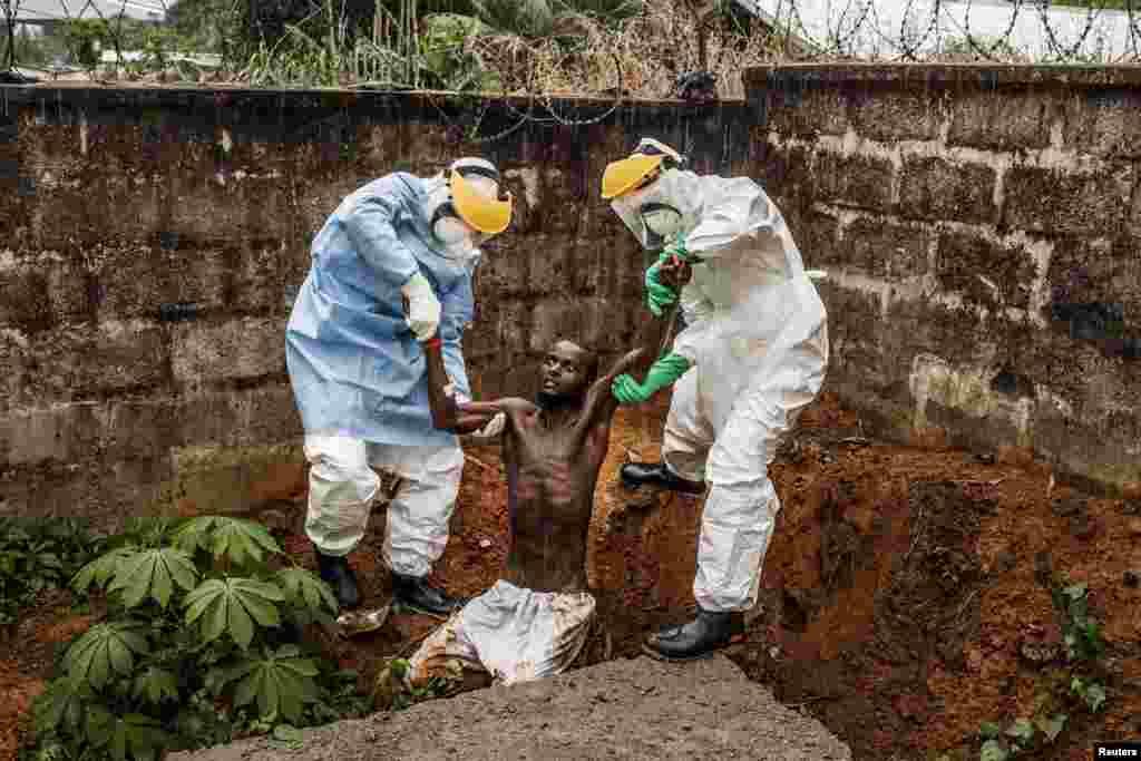 """Американский фотограф Пит Мюллер получил первый приз в категории """"Главные новости. Истории"""". Он снял серию фото, посвященных эпидемии лихорадки Эбола в Африке. На одном из снимков сотрудники лечебницы для зараженных во Фритауне (Гвинея) возвращают обратно пациента, пытавшегося бежать."""