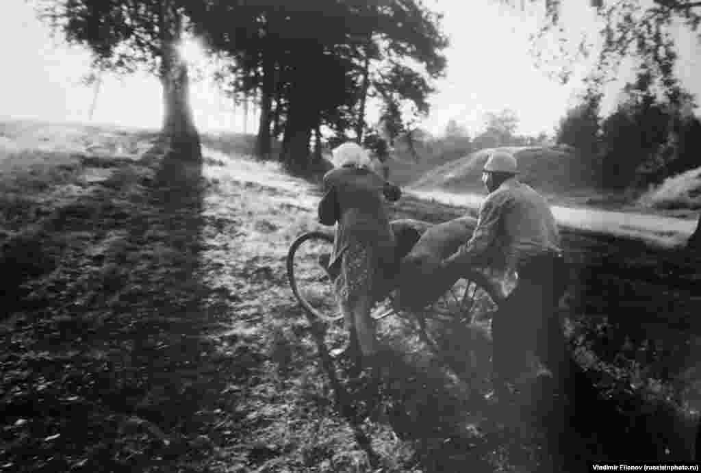 Пара толкает велосипед по весенней грязи, 1980 год