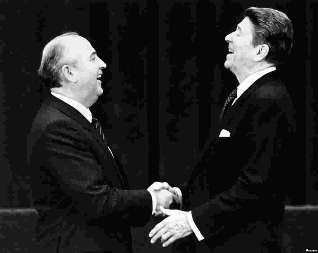 """Март 1985 года. Михаил Горбачев избран новым генеральным секретарем ЦК КПСС. Новый лидер обещает проводить более открытую и дружелюбную внешнюю политику и начать серьезные перемены внутри страны. Подобные заявления советские вожди делали и раньше, но на сей раз все было серьезно. В СССР и в самом деле началась """"перестройка"""". На фото – Михаил Горбачев и президент США Рональд Рейган приветствуют друг друга во время одной из их первых личных встреч"""
