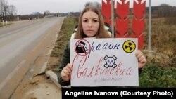 Ангелина Иванова с плакатом против свалки на фоне стелы с названием Палкинского района Псковской области