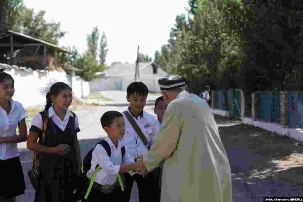 Школьники здороваются со старейшиной села Сексената, идущим в мечеть. Ташкентская область