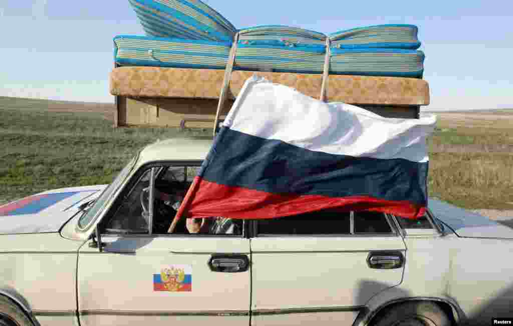 Автомобиль с развивающимся флагом России проезжает около портового города Феодосия после аннексии РФ Крымского полуострова.(Shamil Zhumatov, Reuters)