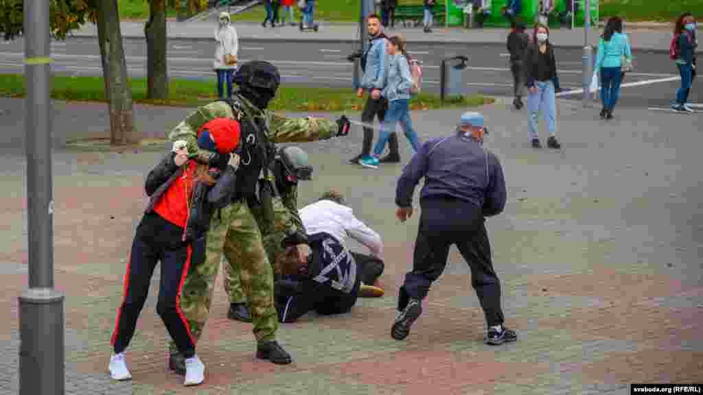 Боец в форме цвета хаки без опознавательных знаков держит девушку за шею, одновременно применяет газ в отношении другого протестующего. 27 сентября, Гродно.