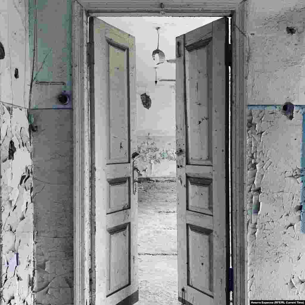 """Дверь в один из кабинетов школы №1. 24-летний Камболат Баев вспоминает, что завуч запрещала детям пить: """"Она говорила: """"В рот наберите, прополоскайте, но не проглатывайте, потому что потом жажда еще сильнее будет"""". Это было первого [сентября]. Второго начали выводить в туалет нас, в раздевалки. И мы там проводили махинации, пока террористов не было, как-то у крана умудрялись воды попить. Потом они это узнали и перестали нас пускать. В итоге мы ходили в здание школы, просто в разные кабинеты: в один мальчики, в другой – девочки. А третьего сентября уже все, уже никто воду не давал – цветы ели""""."""