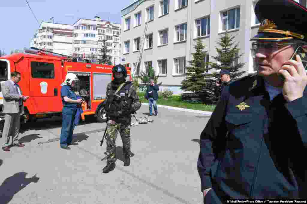 Law enforcement and employees of the Emergencies Ministry stand outside of Kazan's School No. 175. To assist victims, the government has pledged to pay each affected family 1 million rubles (about $13,500) and to allocate to each of the wounded the ruble-equivalent of $2,700 to $5,400, AP reported.