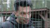 Iranian migrant Amir Chani speaks with Current Time through the fence surrounding Latvia's Mucenieki detention center for illegal migrants. A recent outbreak of COVID-19 cases led to all of the center's 262 residents being placed under quarantine.