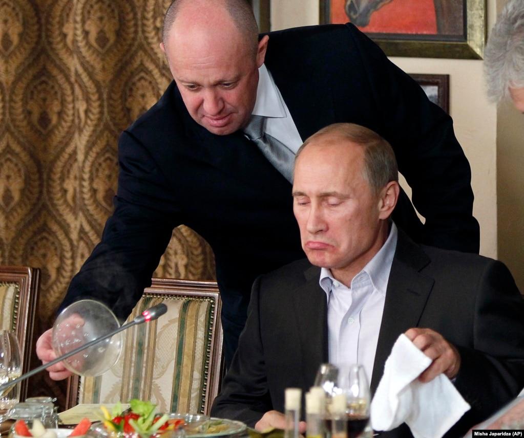 Предприниматель Евгений Пригожин (слева) обслуживает Владимира Путина в своем ресторане в пригороде Москвы