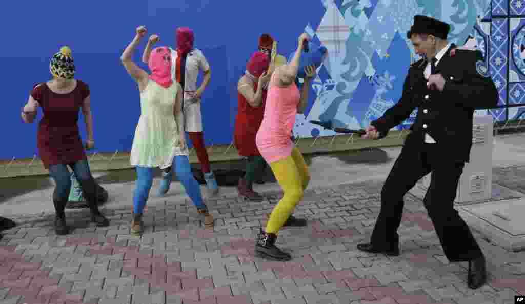 Представитель казачества нападает на Надежду Толоконникову во время акции протеста панк-группыPussy Riot на улице в Сочи. 19 февраля. (Morry Gash, AP)