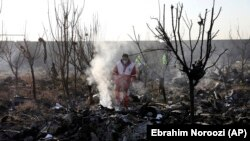 Rescue workers search the scene where an Ukrainian plane crashed in Shahedshahr, southwest of Iran's capital, Tehran, on January 8, 2020.