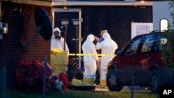 Работники ФБР в костюмах химической защиты осматривают дом после серии рициновых отравлений