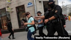 Law enforcement officers are shown detaining journalists in a photograph taken by a Reuters photographer just moments before his own detention in Minsk on July 28.