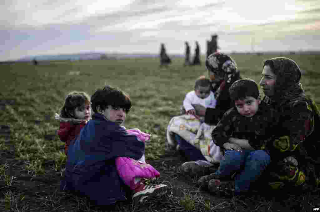 Сирийская семья Курдов сидит близ Турецко-Сирийской в провинции Шанлиурфа. (AFP/Bulent Kilic)