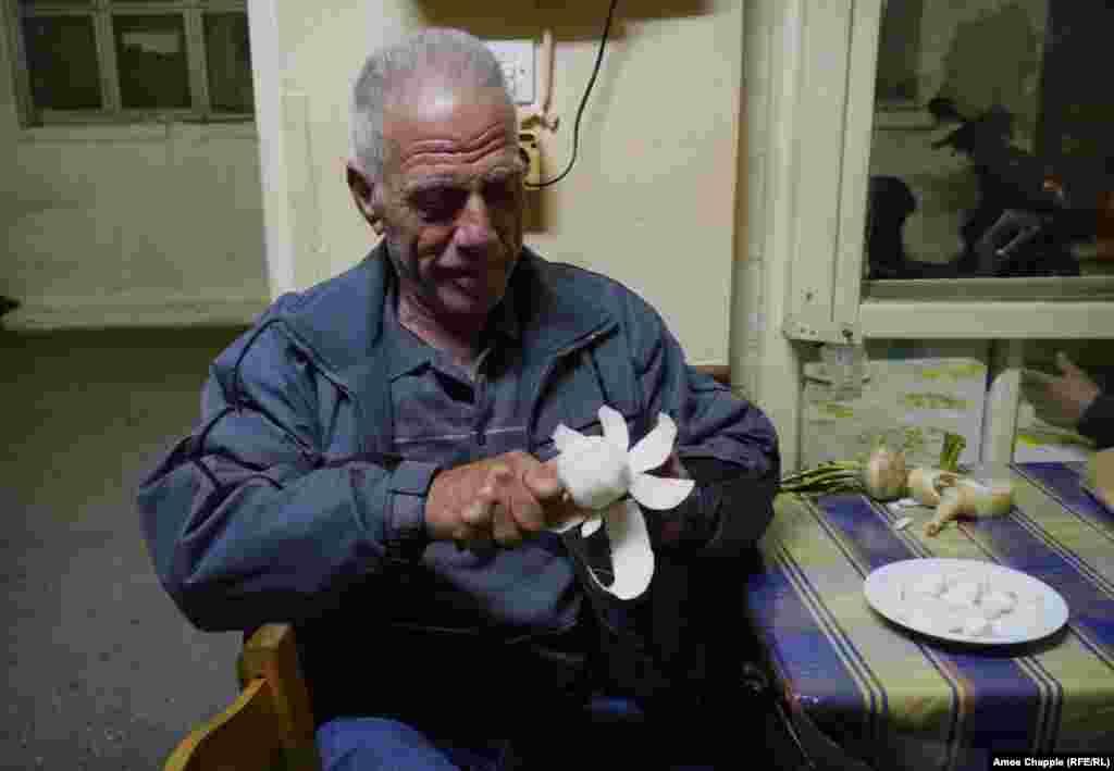Пенсионер Георгиос Коларас, в прошлом каменщик, чистит репу в дверях таверны