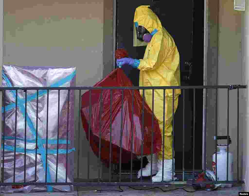 Работникив защитных костюмах убирают квартиру, в которой проживалчеловек с вирусом Эбола. Даллас, Штат Техас, США. 6 октября 2014