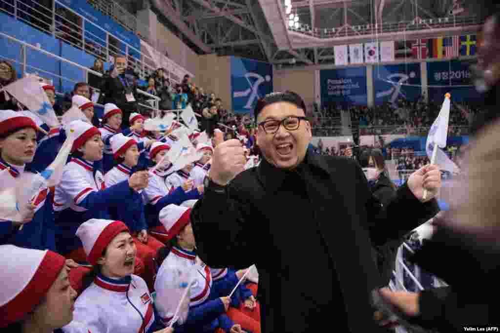 """Мужчина, изображающий из себя северокорейского лидера Ким Чен Ына, позирует на фоне болельщиц из КНДР. Позже мужчину ненадолго задержала полиция и попросила покинуть спортивную арену. """"Я родился с этим лицом, я должен с ним жить"""", – сказал он журналистам. 14 февраля 2018"""