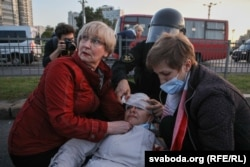 A law enforcement employee bandages the head of a woman injured in a crackdown by riot police on protesters in Minsk on September 23, 2020.
