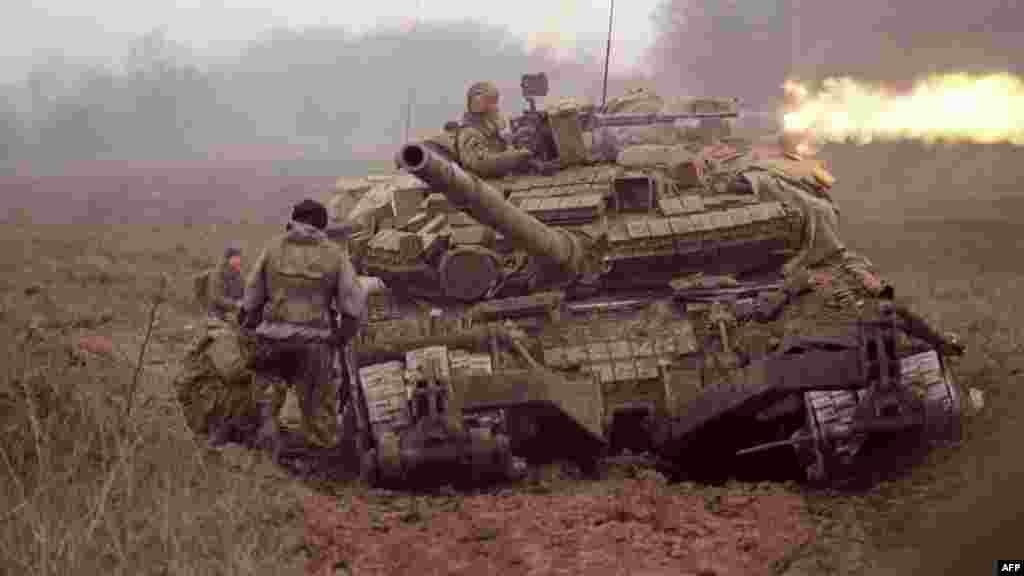 На фото – военный стреляет из пулемета на танке вблизи чеченского села