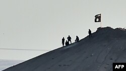 """Боевики экстремистской группировки """"Исламское государство"""" подняли свой флаг на горе в сирийском городе Кобане, который по-арабски называется Айн аль-Араб"""