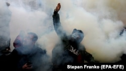 Ukrainian activists throw smoke flares during an October 30, 2020 rally outside Kyiv's Constitutional Court building. The demonstrators demanded that the judges come out and explain their reasons for ruling against criminal penalties for false financial disclosures by officials.