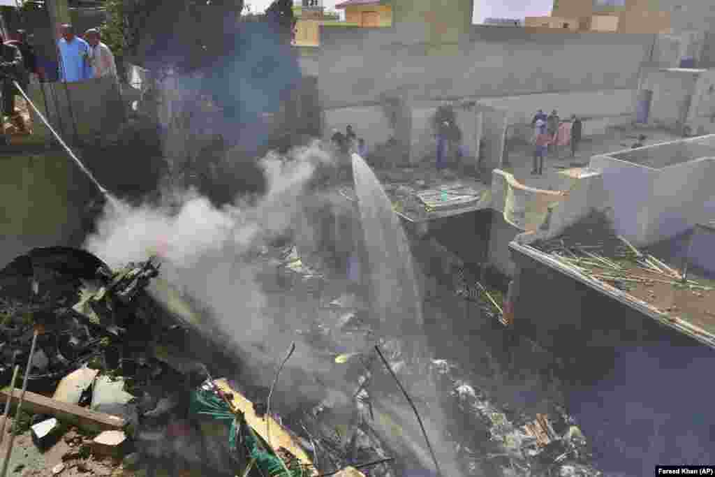 Спасатели тушат пожар, вызванный авиакатастрофой в Карачи, Пакистан, 22 мая 2020 года. В результате трагедии погибли 98 человек