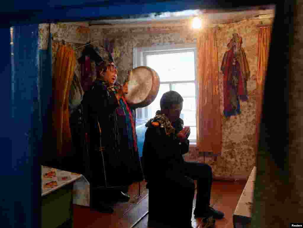 """По поверьям тувинцев, обычные люди не могут стать шаманами по своему собственному желанию. Кто именно будет шаманом – решает дух, который вселяется в тело человека На фото – Анисия Монгуш из общества """"Дунгур"""" (бубен) изгоняет злых духов во время спиритического сеанса"""