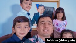 Артист Джахангир Позилжонов с детьми на фоне портрета президента Узбекистана. Кадр из видеоклипа
