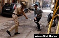 Полицейский бьет палкой нарушителя карантина на улице Нью-Дели, Индия. 25 марта 2020 года. Фото: Reuters