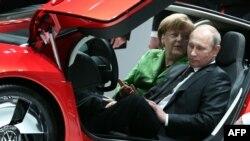 Канцлер Германии Анджела Меркель и президент РФ Владимир Путин позируют в автомобиле Volkswagen XL 1 Hybrid на выставке в Ганновере 8 апреля 2013 года