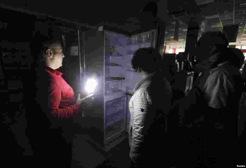 Торговцы показывают свой товар покупателям, освещая его фонарем