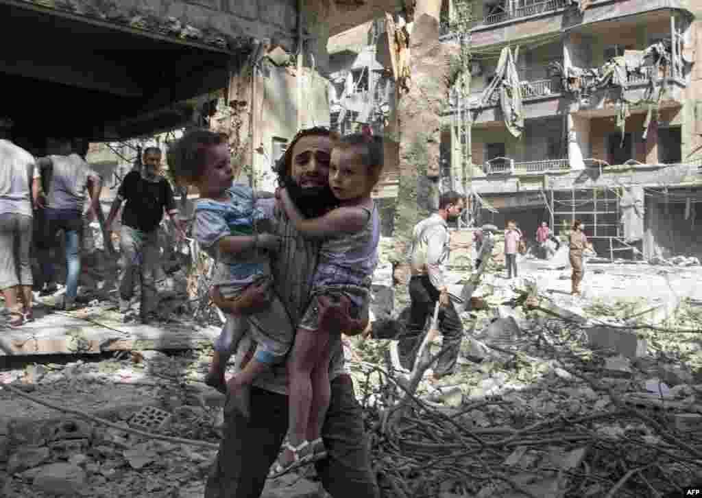 """Бомбы не выбирают цели - мужчина несет своих дочерей через развалины в северном городе Алеппо, который сейчас контролируется ИГИЛом и """"Фронтом аль-Нусра"""", 17 сентября 2015"""