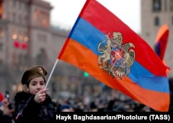 A girl holds an Armenian flag during a March 1, 2021 rally on downtown Yerevan's Republic Square to support Armenian Prime Minister Nikol Pashinian.
