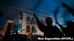 Tbilisi supporters of the ruling Georgian Dream celebrate on election night on October 2 before a campaign poster for incumbent city Mayor Kakha Kaladze.