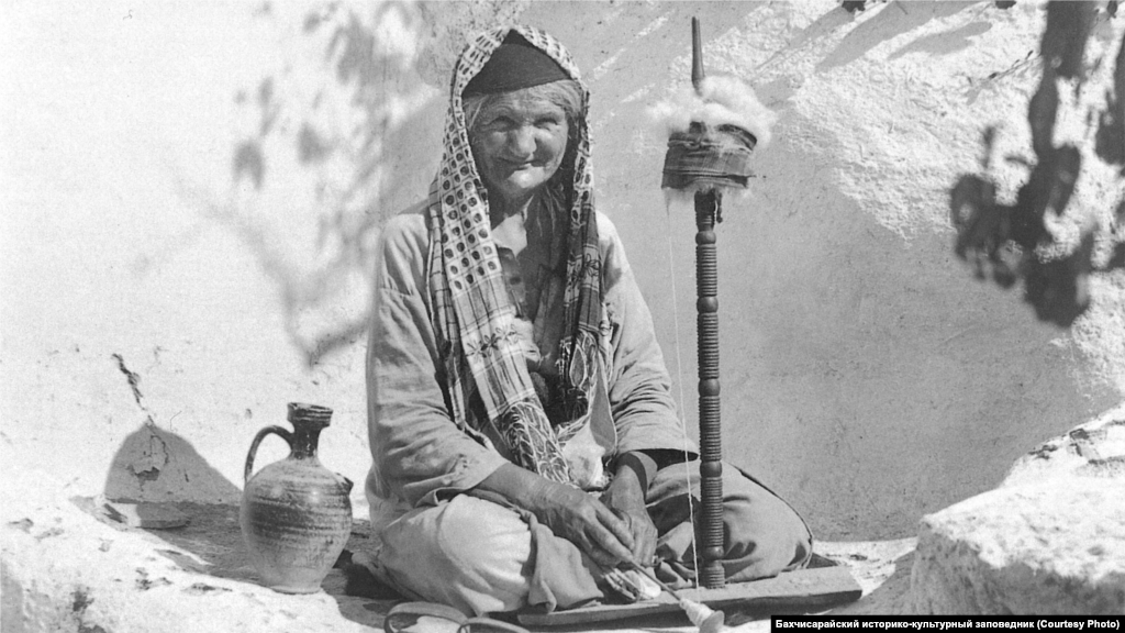 """Прядильщица, 1920-е Самую известную крымскую легкую ткань – """"атму"""" – делали из хлопка и льна. Работали вручную – такие прялки были во многих домах крымских татар. Из ткани шили одежду, покрывала и полотенца. Прядением в основном занимались женщины, ткачеством занимались и мужчины-ремесленники, которых объединяли в цех """"безазы"""""""