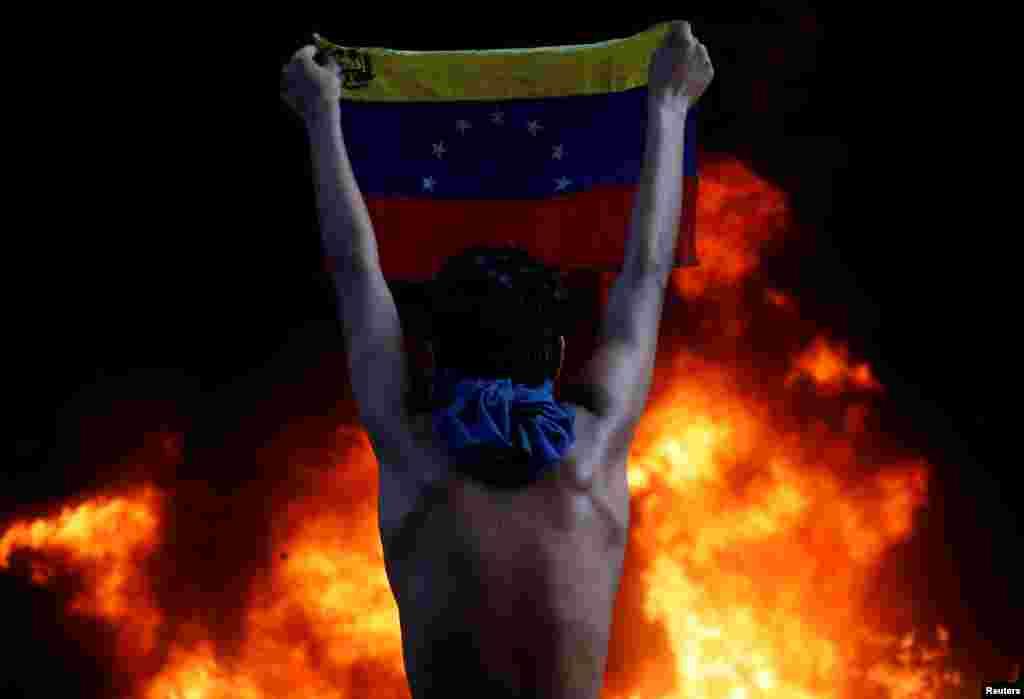 """Массовые протесты в Венесуэле против политики президента Николаса Мадуро в июне 2017 года. Мадуро и его предшественник Уго Чавес пытались построить в Венесуэле социализм и массово национализировали предприятия. Эта политика плюс падение цен на нефть, которая была главным экспортным товаром страны, привели к тяжелейшему экономическому кризису, голоду, дефициту товаров и эмиграции из Венесуэлы нескольких миллионов человек. Несмотря на кризис, Мадуро, которого поддерживают в Кремле, отказывается покидать свой пост. Он винит в проблемах в Венесуэле """"заговор"""", в котором якобы участвуют США и другие враги страны"""