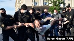Belarus' riot police officers detain an opposition supporter during a gathering to support candidates seeking to challenge President Alyaksandr Lukashenka.