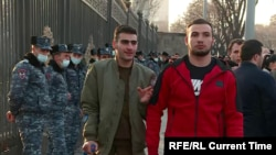 Army soldiers Aik Makhitrian (left) and Georg (no last name given) walk through a protest in Yerevan on March 1, 2021 for Armenian Prime Minister Nikol Pashinian's resignation.