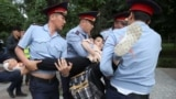 KAZAKHSTAN -- Police officers detain a woman during an opposition rally. June 12, 2019.