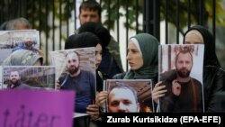 Участники акции в Берлине держат портреты убитого Зелимхана Хангошвили