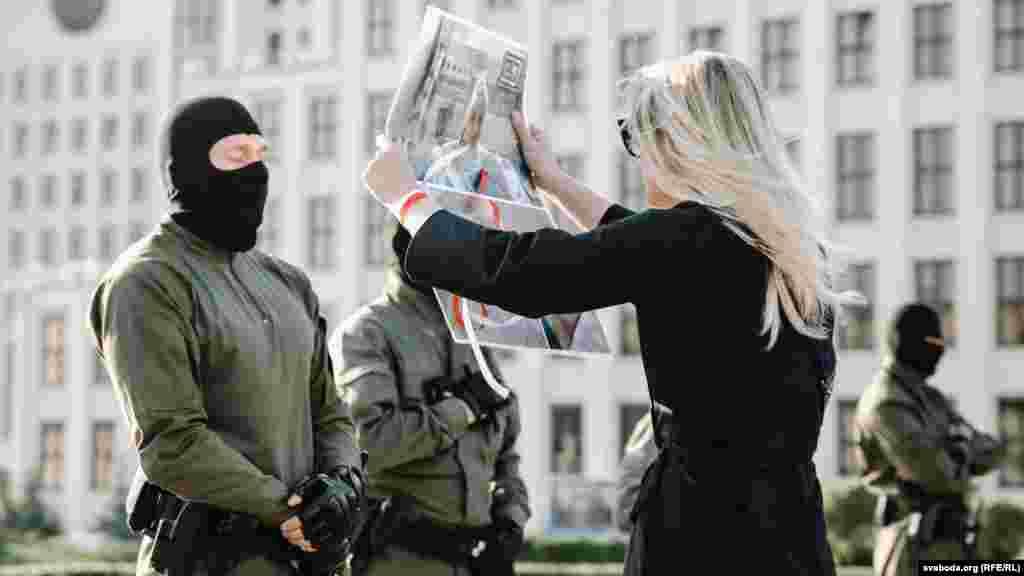 Участница Женского марша показывает силовику, стоящему в оцеплении у Дома правительства, фото с ранеными во время протестов людьми. Он закрывает глаза. 5 сентября, Минск.