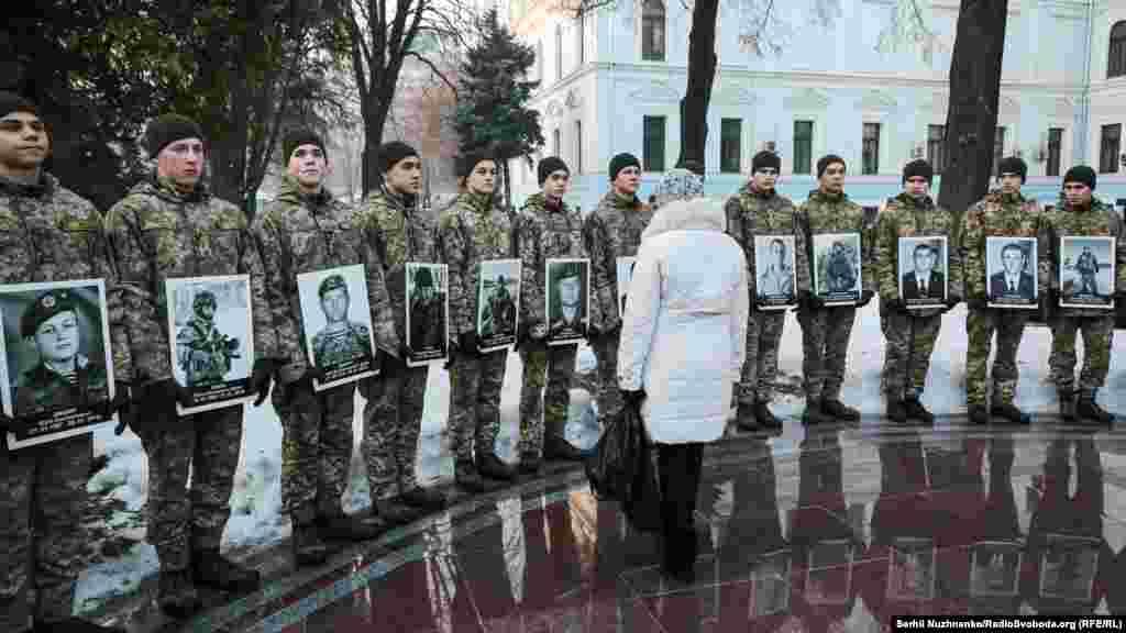 Женщина смотрит на портреты погибших защитников Донецкого аэропорта