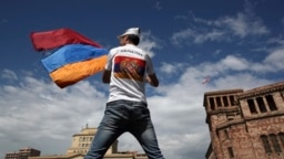 ARMENIA -- A man waves an Armenian flag at the Republic Square in Yerevan, Tuesday, May 8, 2018.