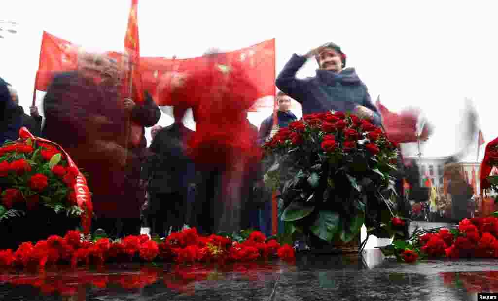 Люди возлагают цветы к памятнику Ленина на Площади независимости в Минске. 7 ноября